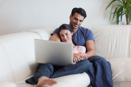 Paar einen Film sehen, w�hrend Popcorn essen mit einem Laptop