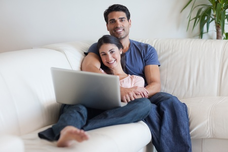 Couple watching a movie with a laptop in their living room photo