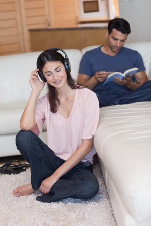 Portrait of a woman listening to music while her fiance is reading a book in their living room photo