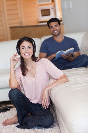 Portrait of a young woman listening to music while her husband is reading a book in their living room photo