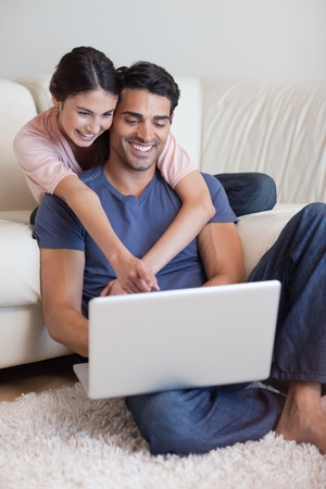 Portrait of a charming couple using a laptop in their living room photo