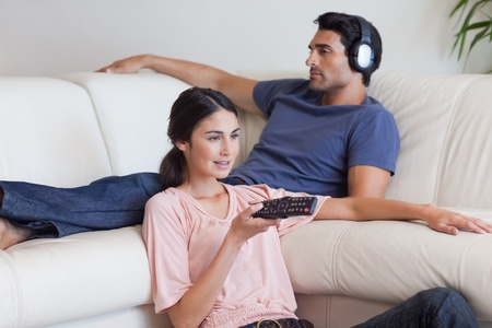 Woman watching TV while her fiance is listening to music in their living room photo