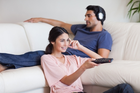 Woman watching TV while her boyfriend is listening to music in their living room photo