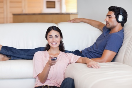 Woman watching television while her husband is listening to music in their living room photo