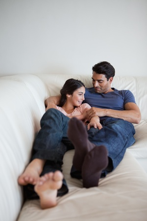 cuddling: Portrait of a couple lying on a couch looking away from the camera