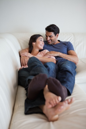 couple talking: Portrait of a young couple lying on a sofa while looking at each other Stock Photo