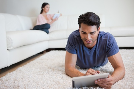 Man using a tablet computer while his girlfriend is reading a book in their living room photo
