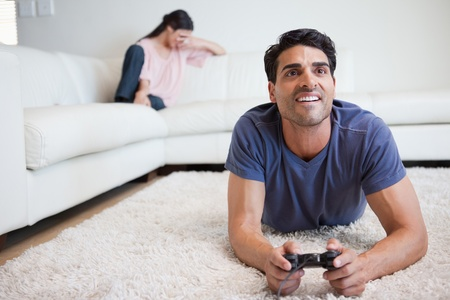 Man playing video games while his fiance is crying in their living room photo
