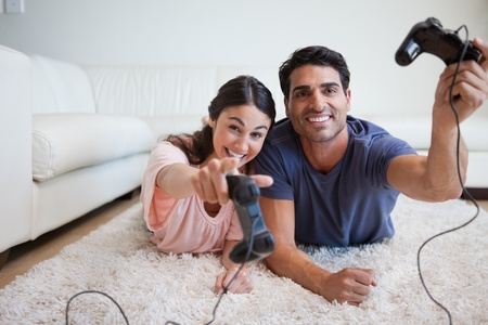 Playful young couple playing video games in their living room photo