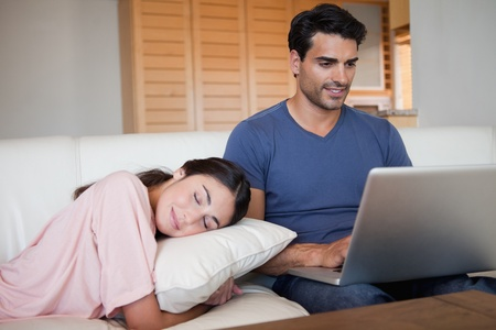 Man using a laptop while his fiance is sleeping in their living room Stock Photo - 11683639