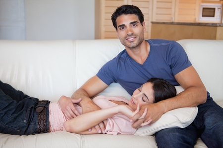 Woman sleeping while his boyfriend is posing in their living room photo
