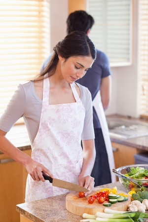 Portrait of a woman chopping pepper while her fiance is washing dishes in their kitchen photo