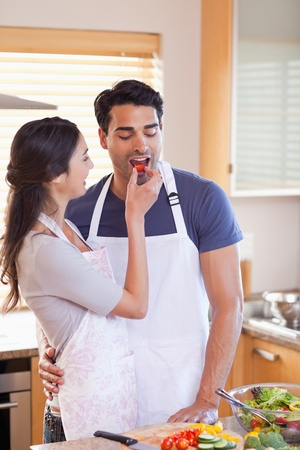 Portrait a woman feeding her husband in their kitchen photo