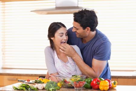 Man feeding his wife in their kitchen photo