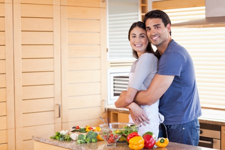Charming couple embracing each other in their kitchen photo