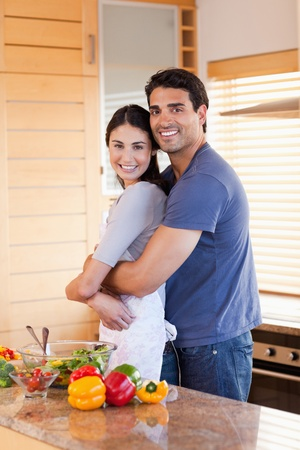 Portrait of a couple embracing each other in their kitchen photo