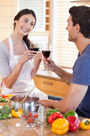 Portrait of a couple having a glass of red wine while cooking in their kitchen photo