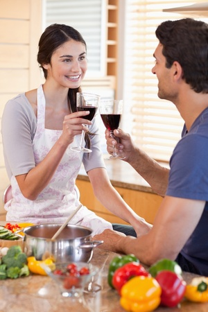 Portrait of a couple having a glass of wine while cooking in their kitchen photo