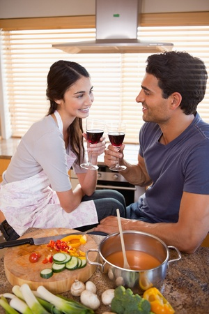 Portrait of a happy couple having a glass of wine while cooking in their kitchen photo