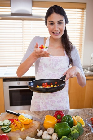 Portrait of a young woman preparing a dish in her kitchen photo