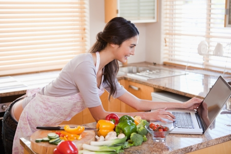 dona de casa: Woman looking for a recipe on the internet in her kitchen