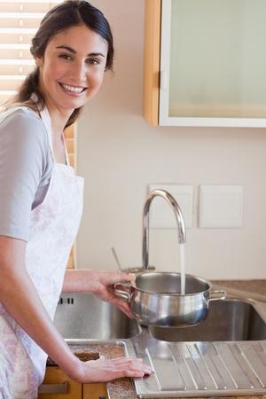 Portr�t einer Frau gie�t Wasser in einem Topf in ihrer K�che Lizenzfreie Bilder