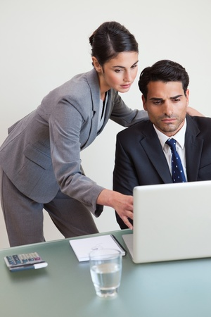 clarify: Portrait of a focused business team working with a laptop in an office Stock Photo