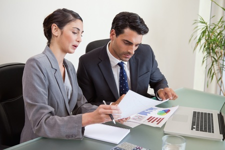 Sales persons working with a notebook in an office photo