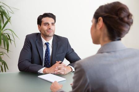 Knappe manager interviewen van een vrouwelijke kandidaat in zijn kantoor Stockfoto