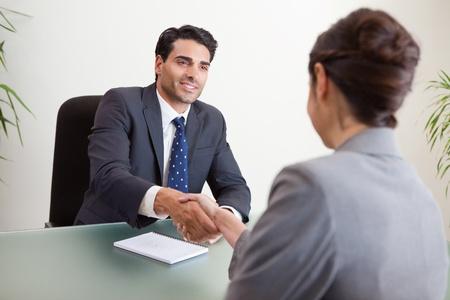 communication occupation: Gestore sorridente intervistando un candidato di sesso femminile nel suo ufficio Archivio Fotografico