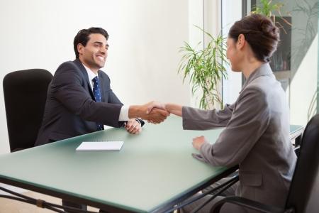 contrato de trabajo: Sonriendo gestor de entrevistar a un solicitante de buena apariencia en su oficina