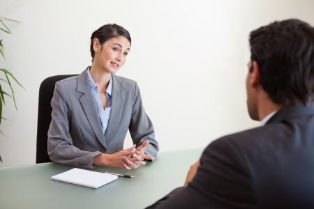dos personas hablando: Gerente de entrevistar a un solicitante de buena apariencia en su oficina