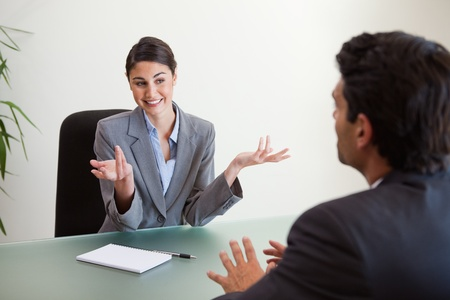 Smiling manager interviewing an employee in her office photo