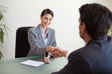 Manager shaking the hand of a customer in her office photo