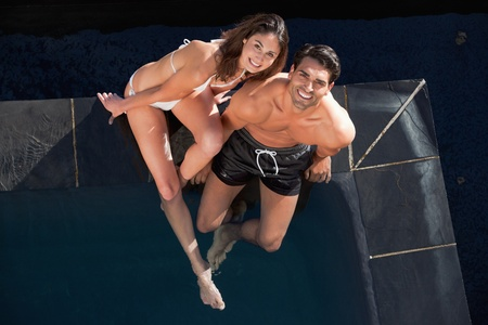 Above view of a smiling couple posing in a swimming pool photo