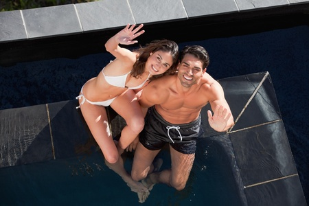 Above view of a smiling couple waving at the camera in a swimming pool photo