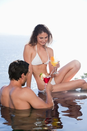 Portrait of a couple having a cocktail in a swimming pool photo