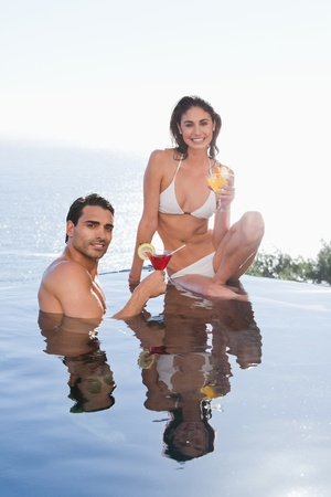 Portrait of a smiling couple having a cocktail in a swimming couple photo