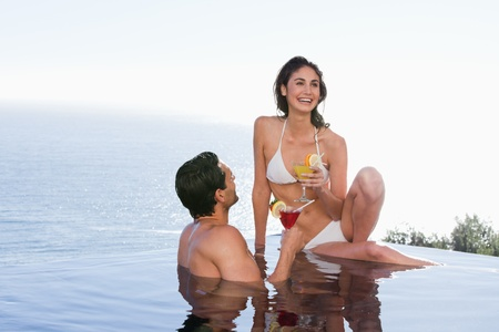 Couple having a cocktail in a swimming pool photo