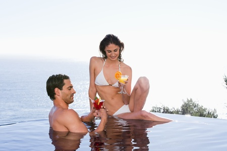 Young couple having a cocktail in a swimming pool photo