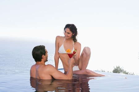 Lovely couple having a cocktail in a swimming pool photo