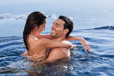 Delighted couple cuddling each other in a swimming pool photo
