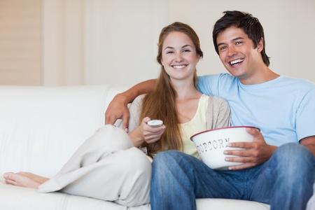 pareja viendo tv: Pareja viendo la televisi�n mientras come palomitas de ma�z en su sala de estar