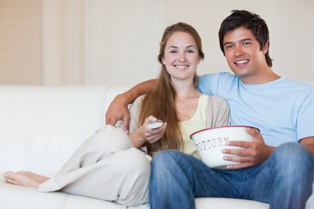 Young couple watching television while eating popcorn in their living room photo