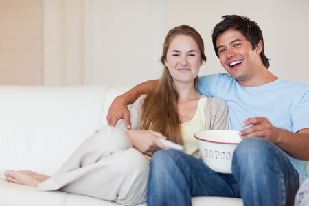 Smiling couple watching television while eating popcorn in their living room photo