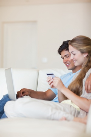 Portrait of a couple shopping online in their living room Stock Photo - 11686276