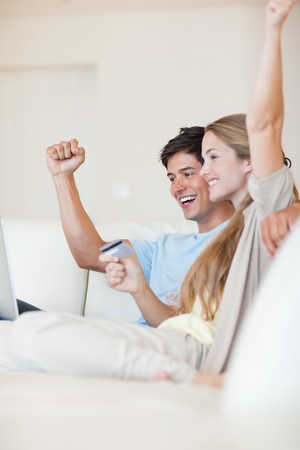 Portrait of a successful couple shopping online in their living room photo