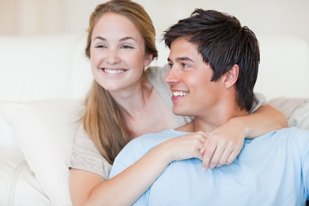 Close up of a young couple posing in their living room photo