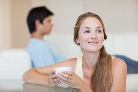 Woman having a tea while her fiance is sitting on a sofa in their living room photo