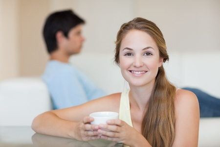 Woman drinking tea while her fiance is sitting on a couch in their living room photo